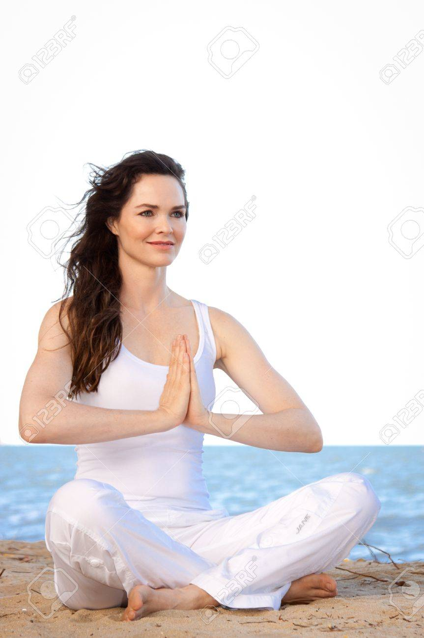 Beautiful healthy & fit young woman meditating on the beach Stock Photo - 12062814