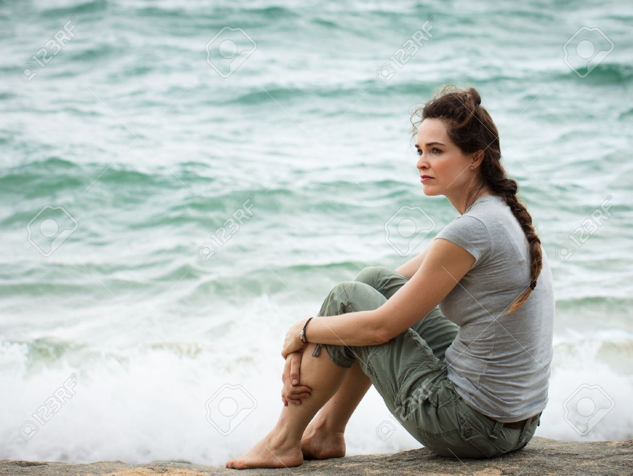 A sad and pensive woman sitting by the ocean deep in thought Stock Photo - 19588355