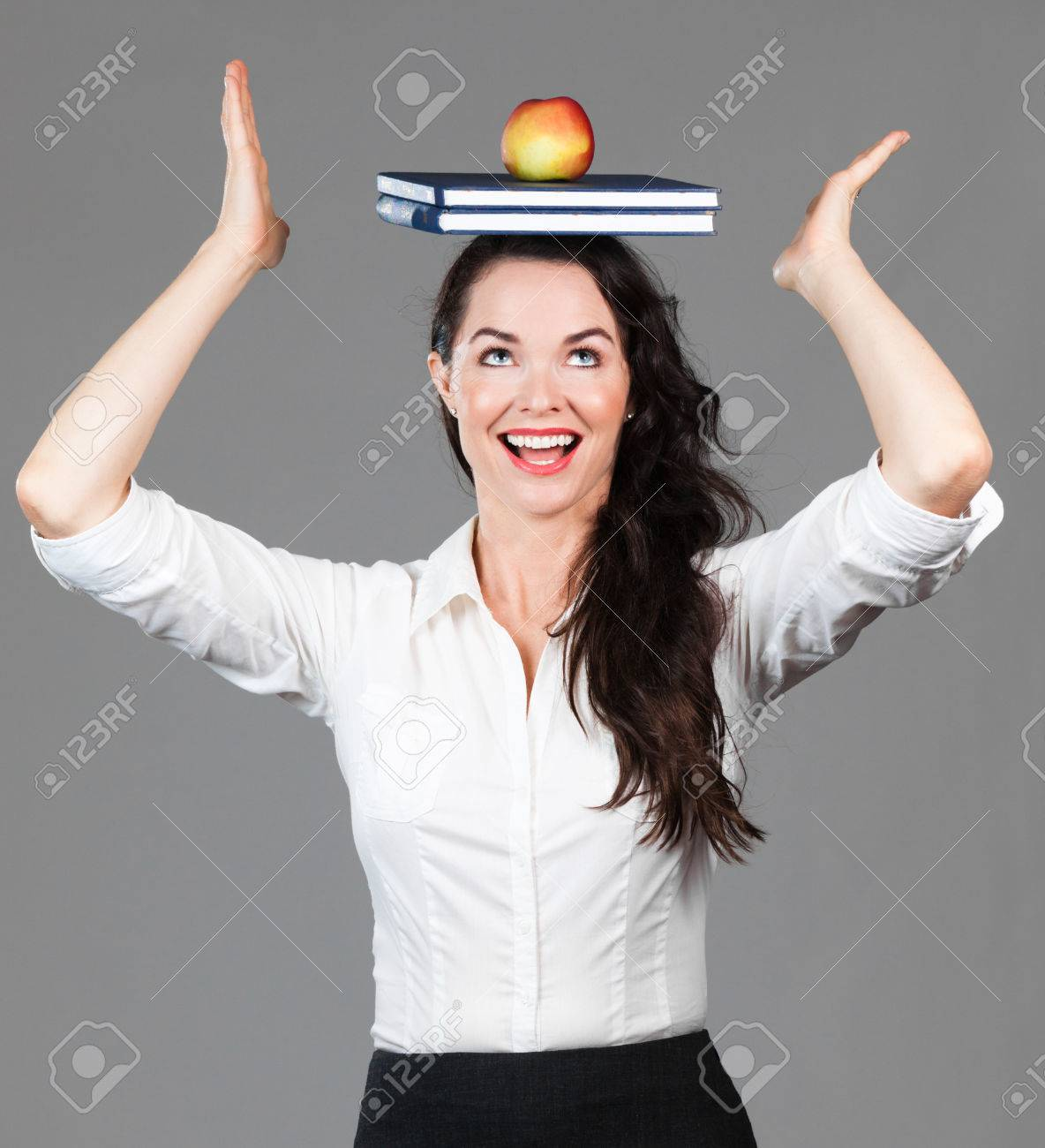 A happy beautiful business woman balancing books and an apple on her head Stock Photo - 26901005