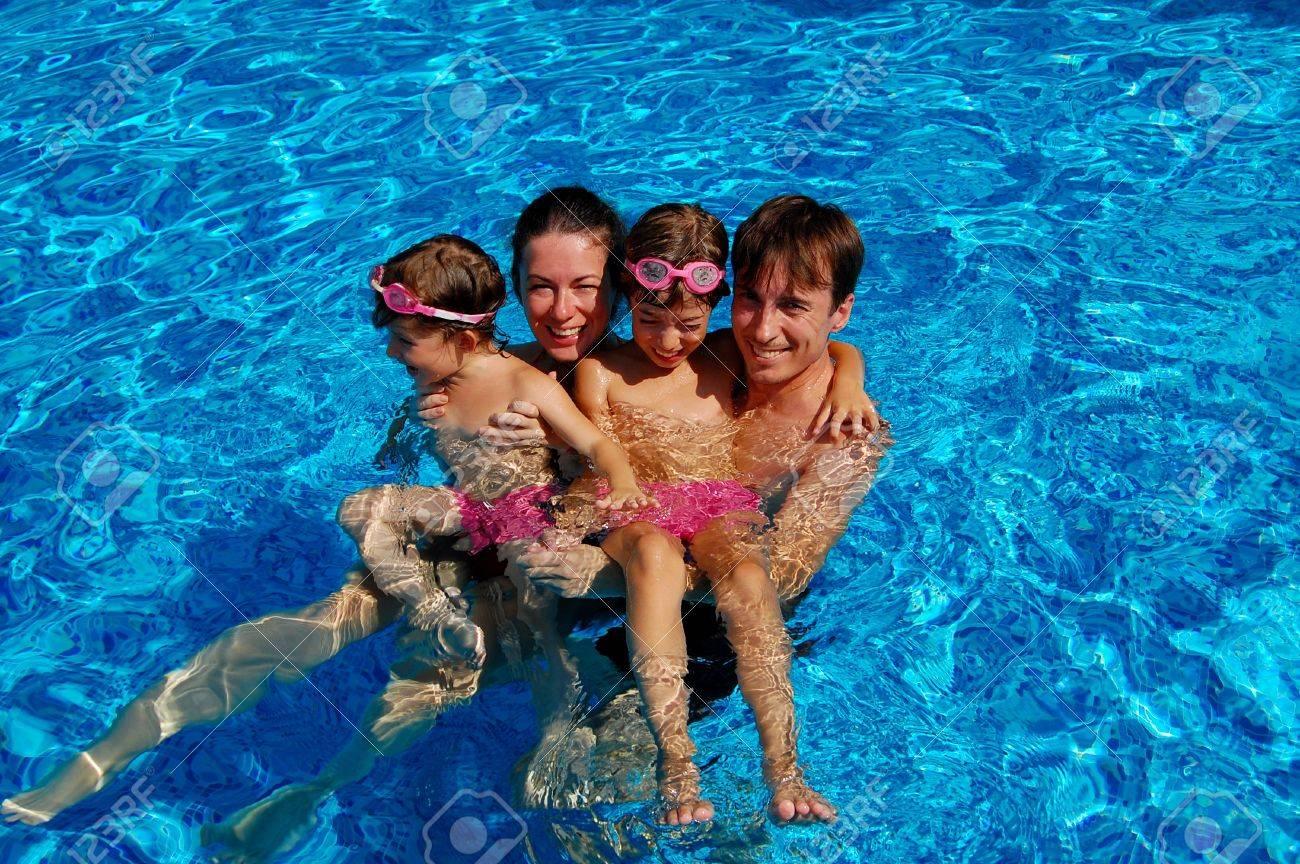 Happy family of four having fun in swimming pool Stock Photo - 9305740