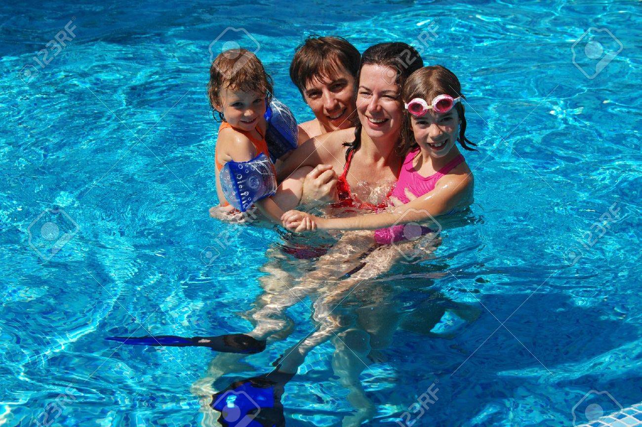 Happy family with two kids having fun in swimming pool Stock Photo - 9337217