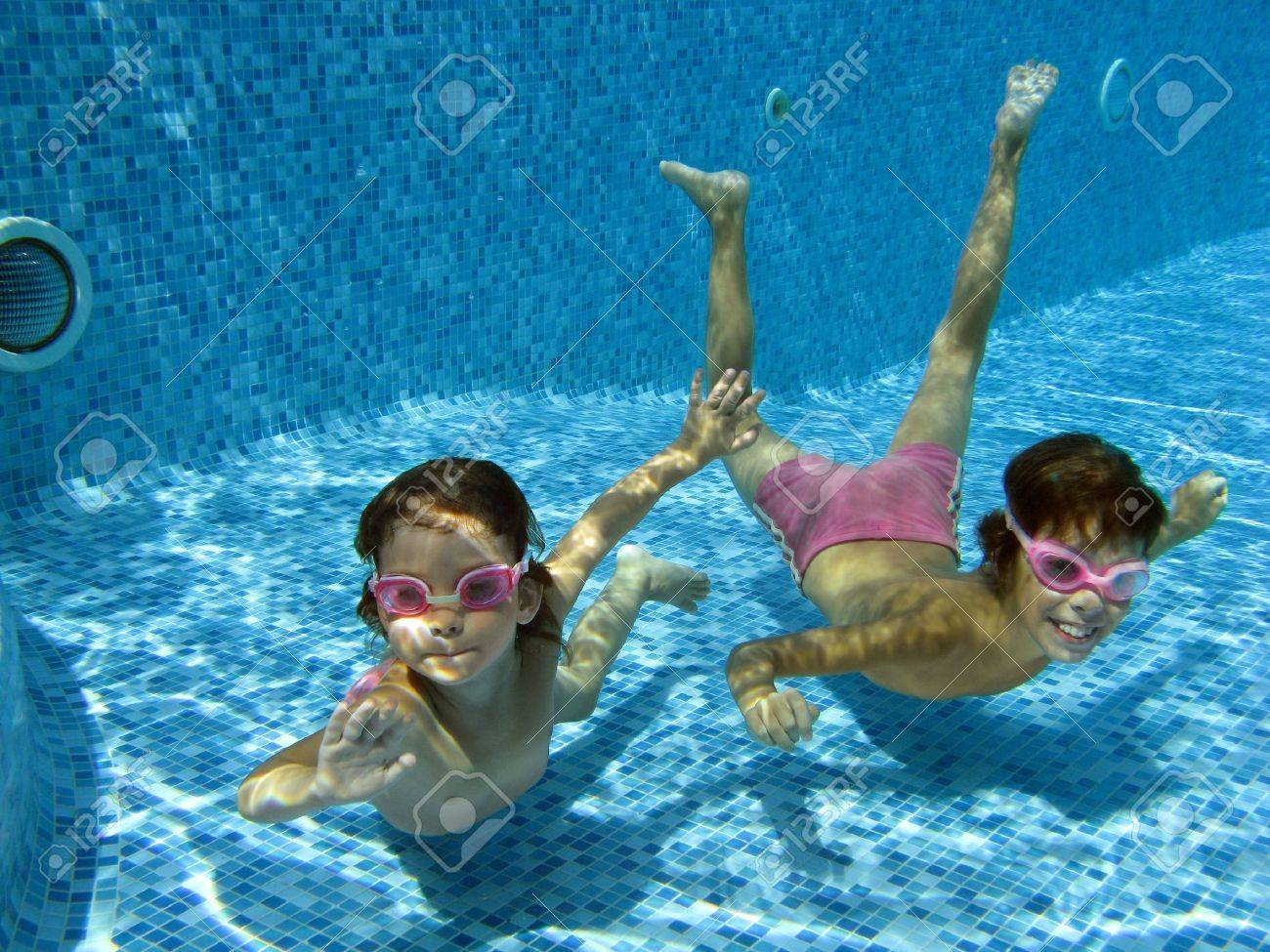 Kids Swimming Underwater two underwater kids in swimming pool stock photo, picture and