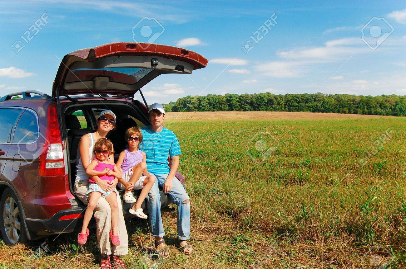 Family of four near their car on vacation Stock Photo - 10531933