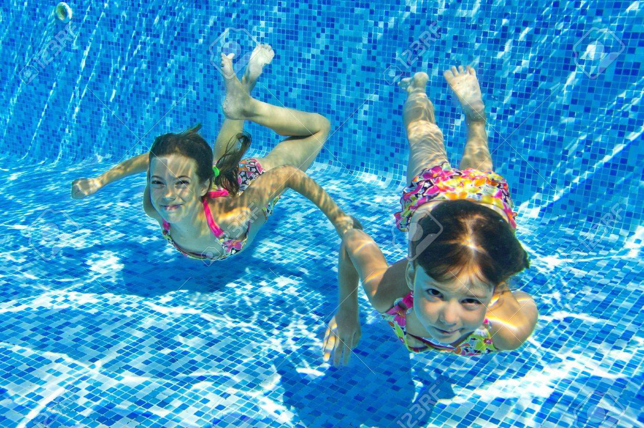 Happy smiling underwater children in swimming pool, beautiful..
