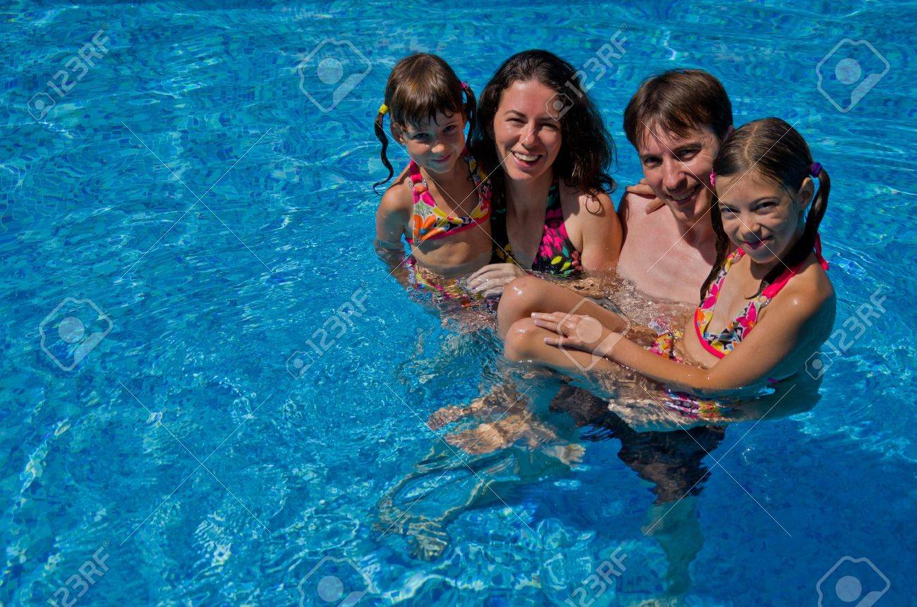 Happy family with two kids in swimming pool  Smiling parents and children on summer vacation swim and having fun  Family sport, active healthy holiday Stock Photo - 14663935