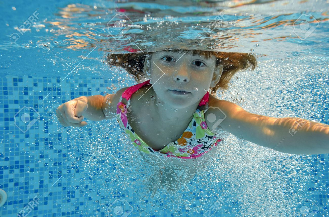Kids Swimming Underwater happy smiling underwater child jumps to swimming pool, beautiful