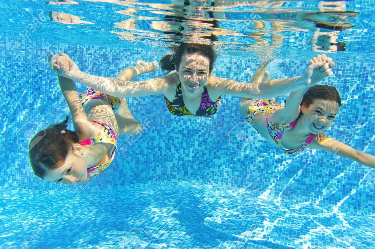 Beautiful Happy Smiling Family Underwater In Swimming Pool. Mother And Children Swim  And Having Fun.