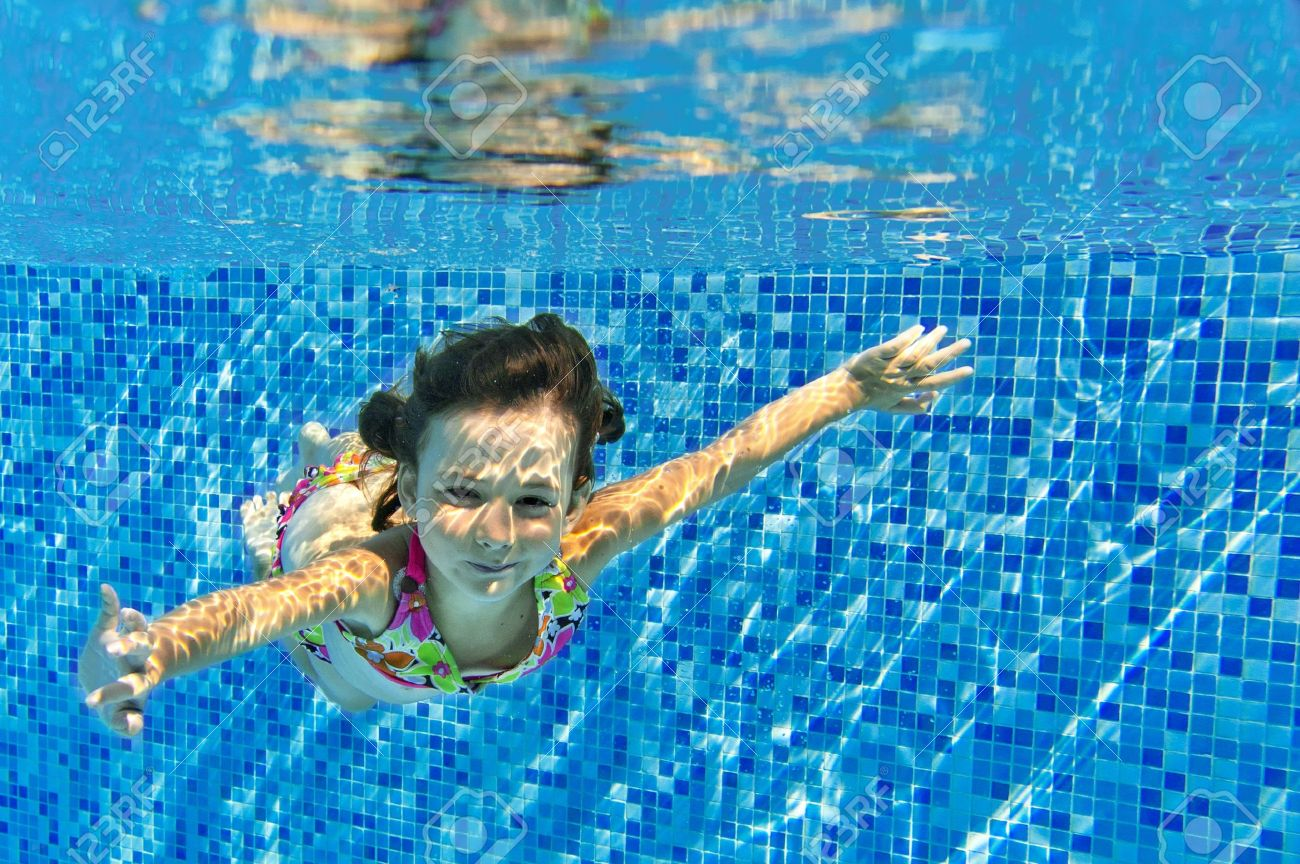 Happy active child swims underwater in pool, beautiful healthy girl swimming and having fun on family summer vacation, kids sport concept - 21976315