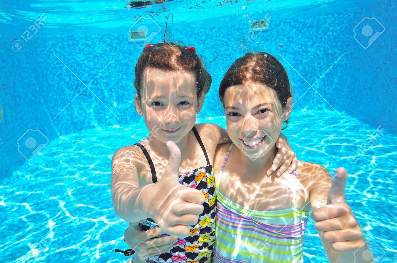 happy active kids swim in pool and play underwater girls diving and having fun - Kids Swimming Underwater
