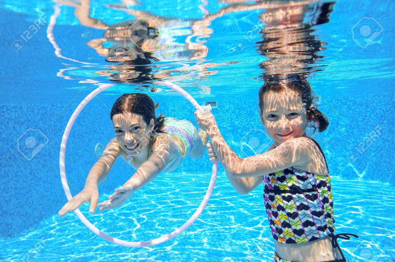 Happy active kids swim in pool and play underwater, girls diving and having fun, children on summer vacation, sport concept - 30533080