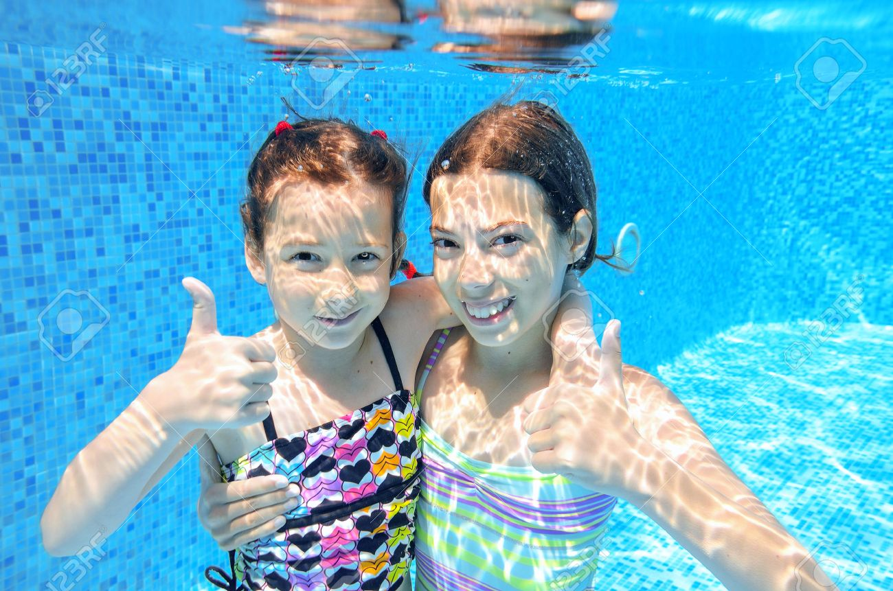 Happy active kids swim in pool and play underwater, girls diving and having fun, children on summer vacation, sport concept - 31252514