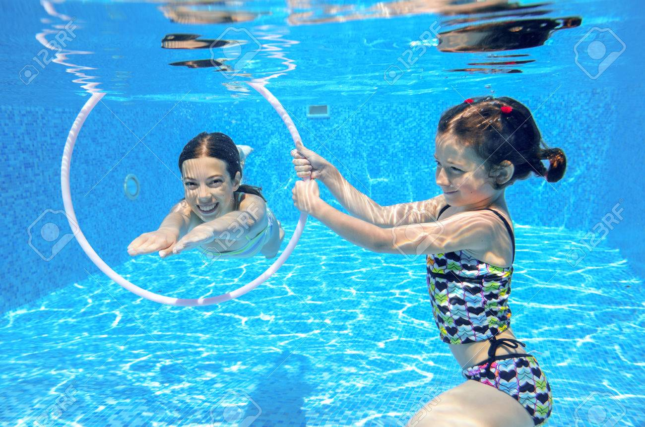 Happy active kids swim in pool and play underwater, girls diving and having fun, children on summer vacation, sport concept - 33092591