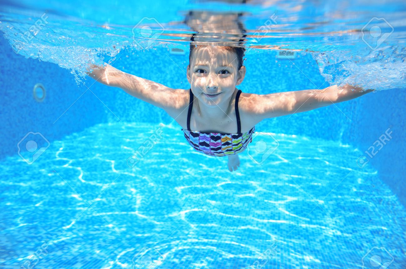 Happy active underwater child swims in pool, beautiful healthy girl swimming and having fun on family summer vacation, kids sport - 33873208