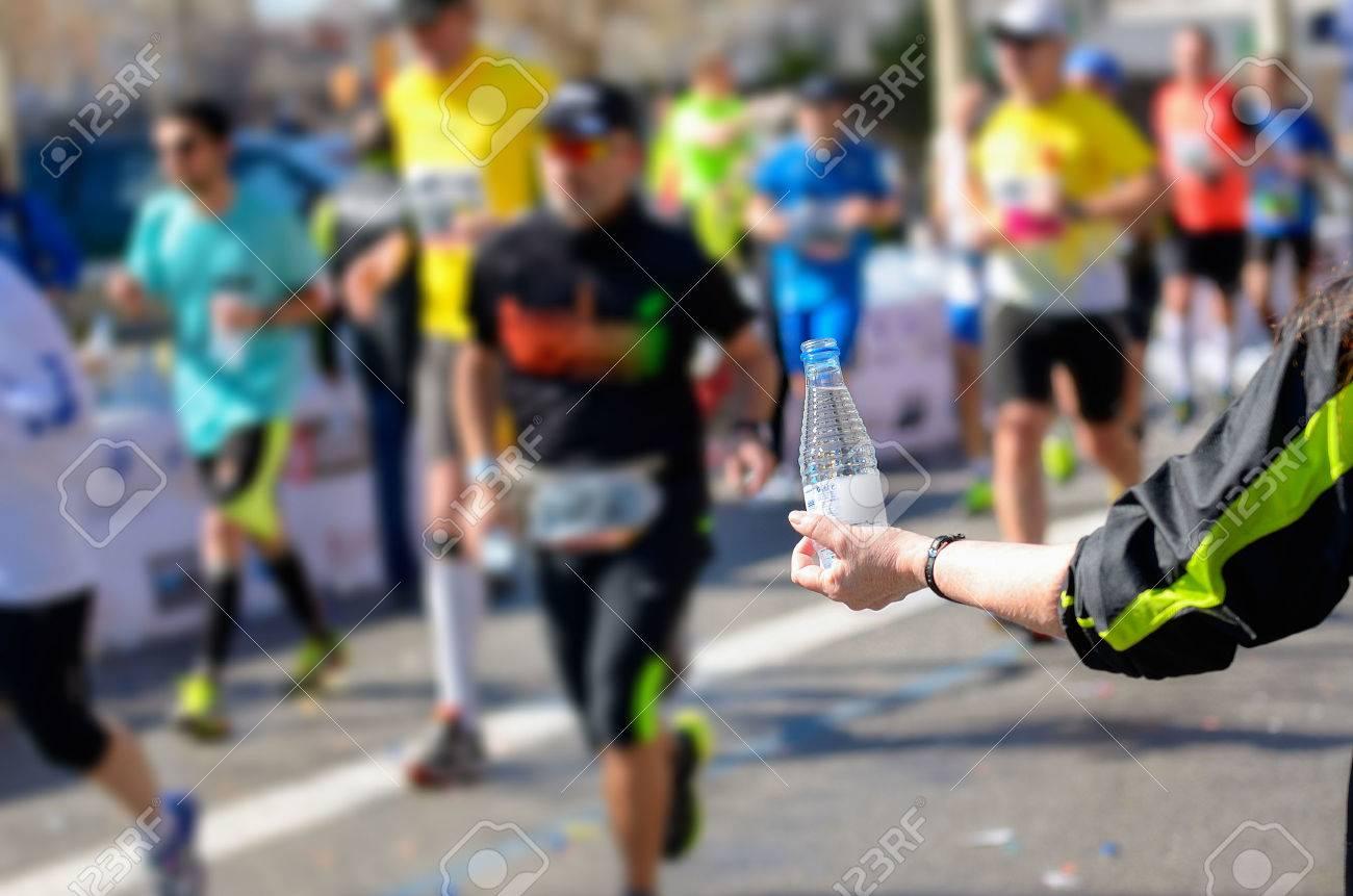 Marathon running race, runners on road, volunteer giving water on refreshment point - 38189712