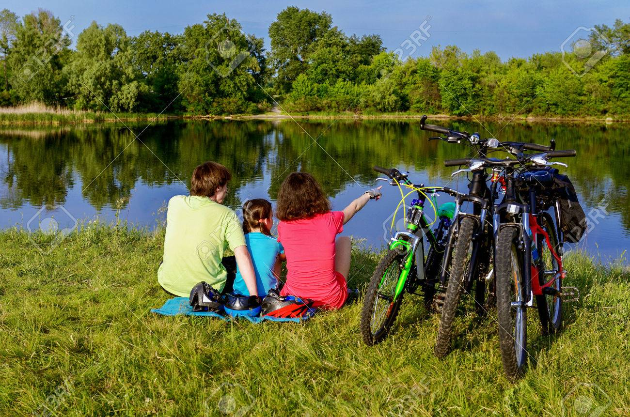 Family bike ride outdoors, active parents and kid cycling and relaxing near beautiful river - 42906784