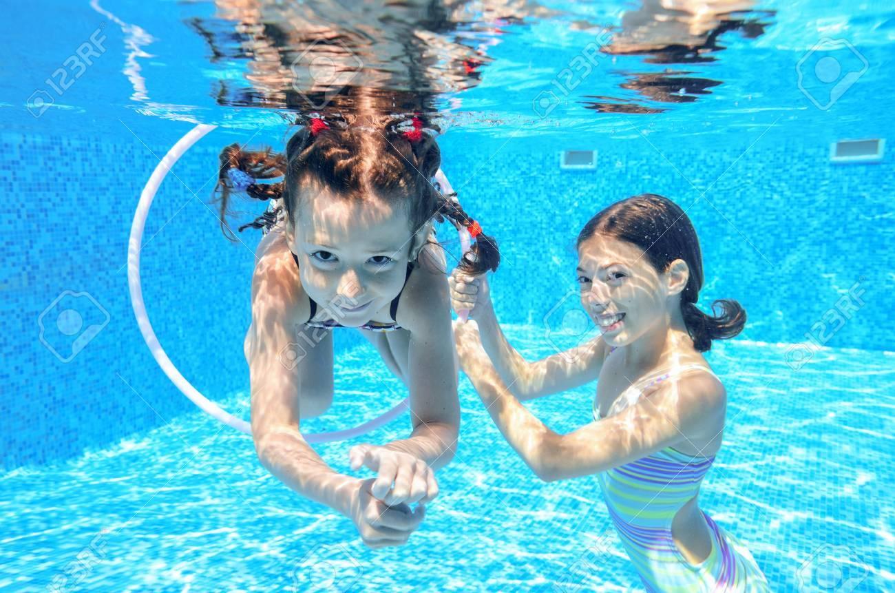 Happy children swim in pool underwater, girls swimming, playing and having fun, kids water sport - 42906785