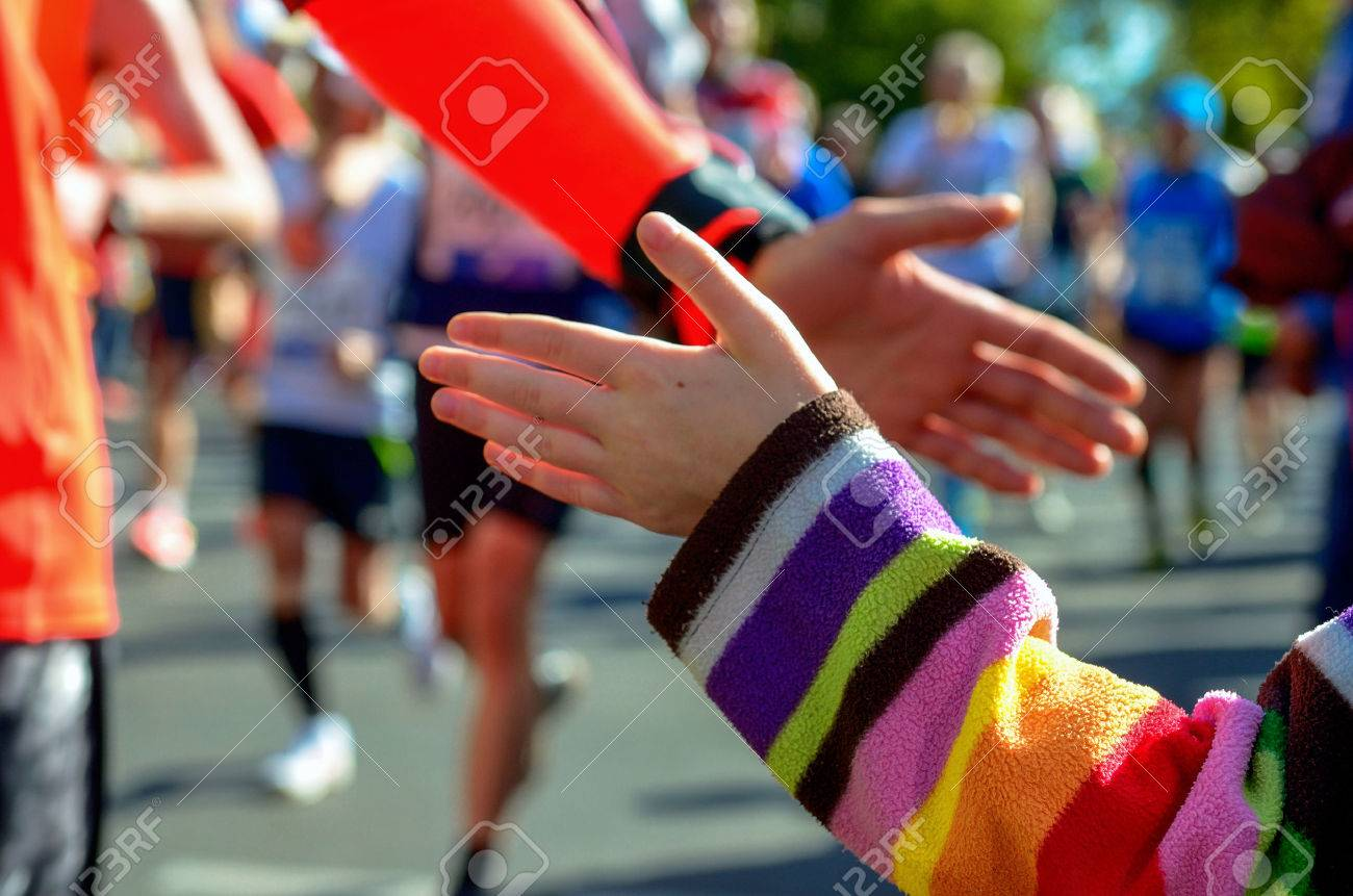 Blurred background: marathon running race, support runners on road, child's hand giving highfive, sport concept - 50939413