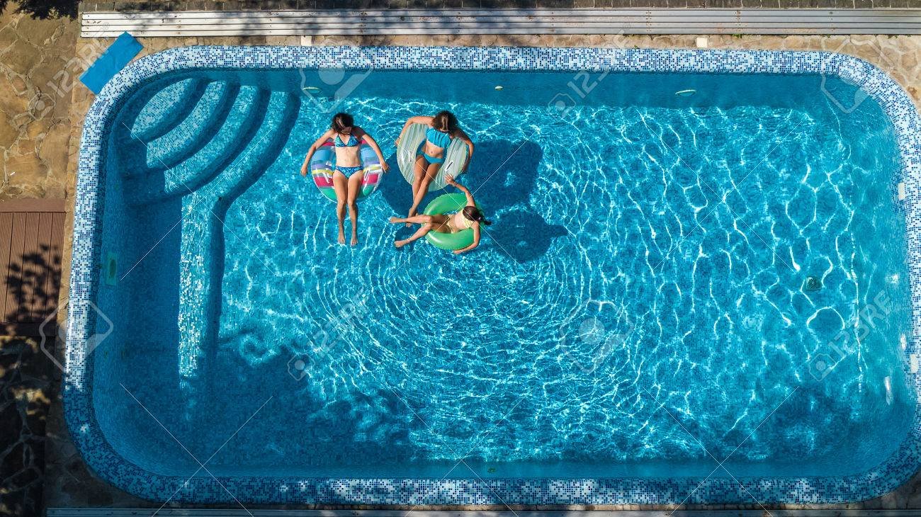 aerial top view of family in swimming pool from above mother and kids swim and