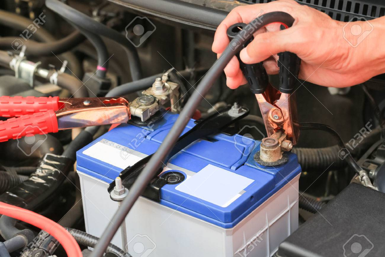 Car mechanic uses battery jumper cables charge a dead battery