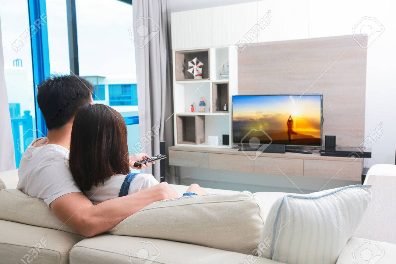 Happy family watches television while sitting on the sofa. - 83163637