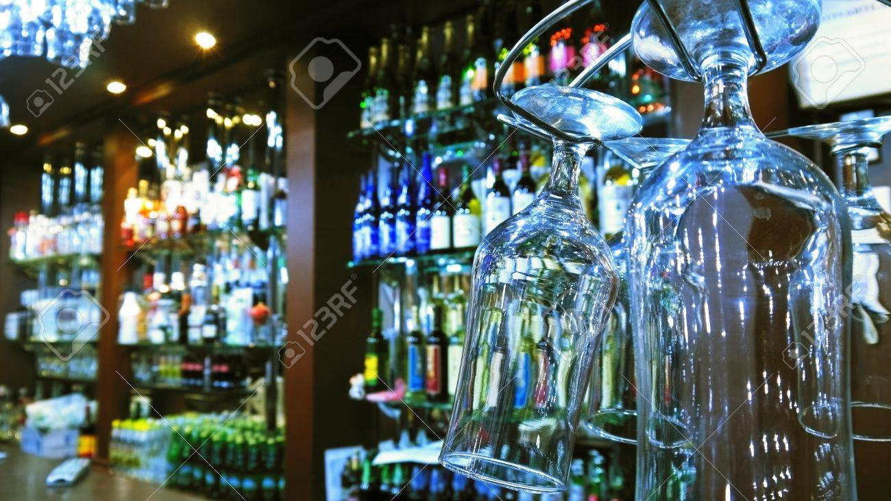 Wineglasses on bar counter with blurred bottles in background Stock Photo - 16963309
