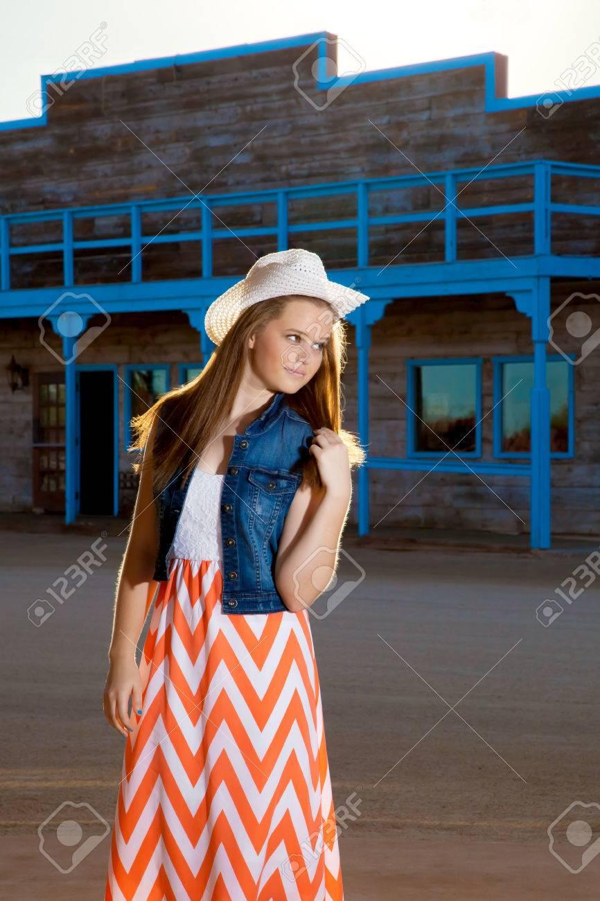 ed8f34764 Una vaquera adolescente que llevaba una falda larga del modelo del galón y  una chaqueta de mezclilla con un sombrero del oeste juega con su pelo ...