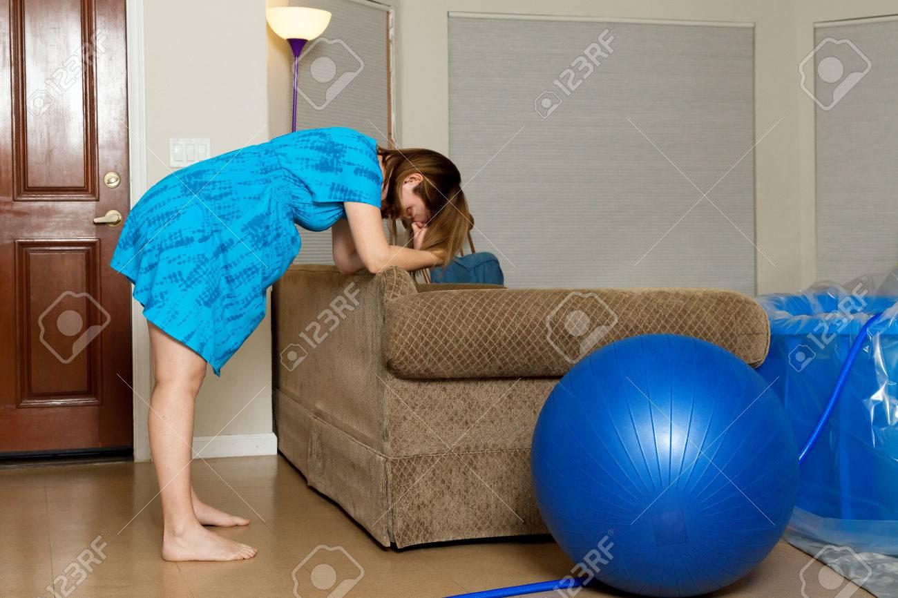 Eine Frau In Den Wehen Lehnt Sich Nach Vorne Auf Die Rückseite Einer ...