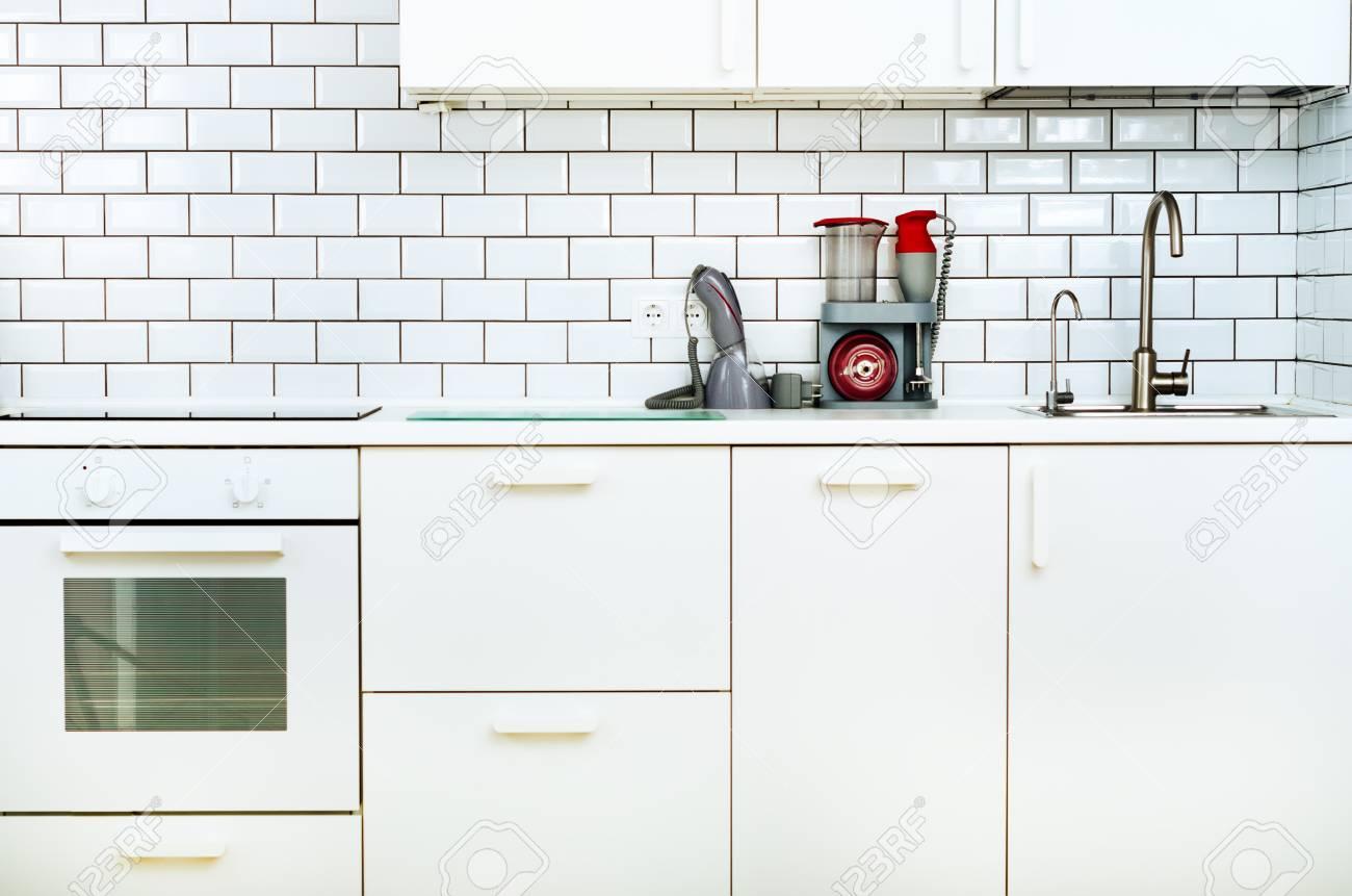 Interno e design minimalista bianco della cucina. Sfondo muro di  piastrelle. Elettrodomestici - frullatore, aspirapolvere, stufa moderna, ...