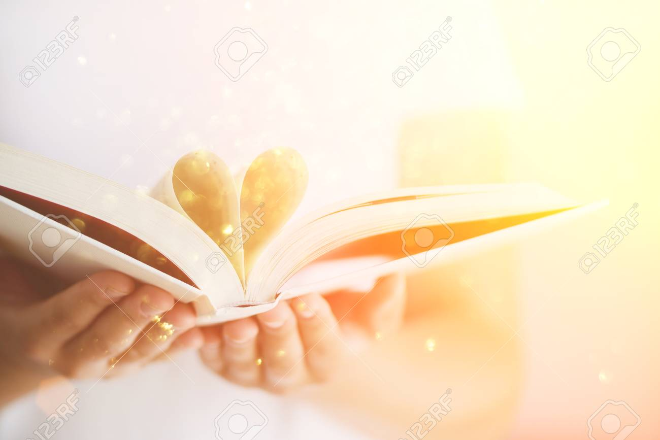 Book with opened pages and shape of heart in girl hands. Copy space. Love concept. Festive background with bokeh and sunlight. Magic fairy tale - 88771187