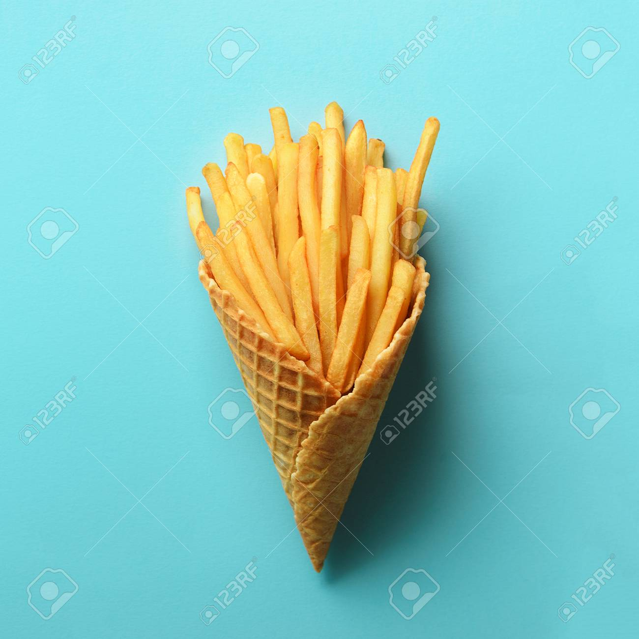 Fried potatoes in waffle cones on blue background. Hot salty french fries with tomato sauce. Fast food, junk food, diet concept. Top view. Minimal style. Pop art design, creative concept - 104932496