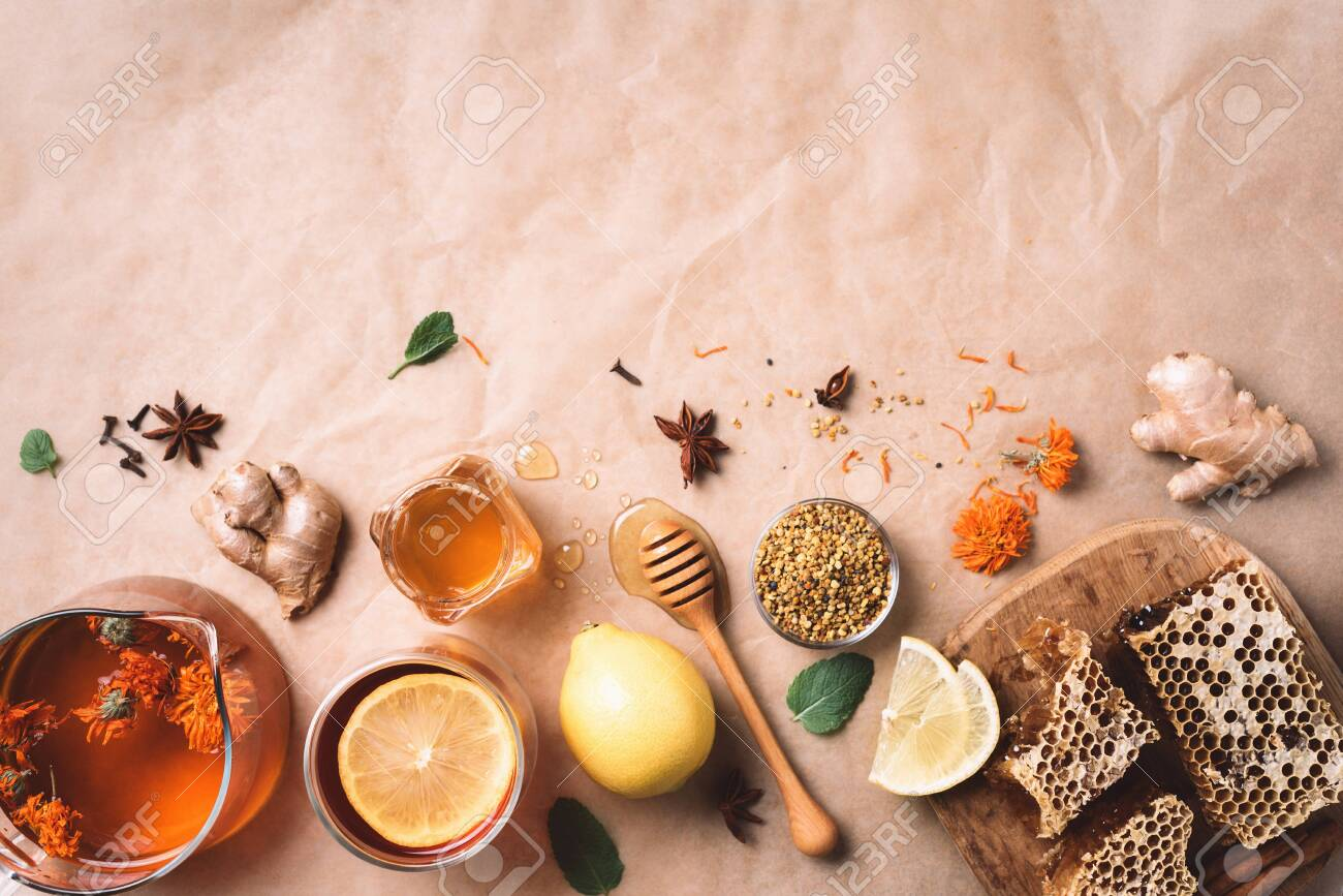 Ingredients for healthy hot drink. Lemon, calendula, ginger, mint, honey, apple and spices over craft paper background. Copy space. Top view. Alternative medicine concept. Clean eating, detox. - 130387549
