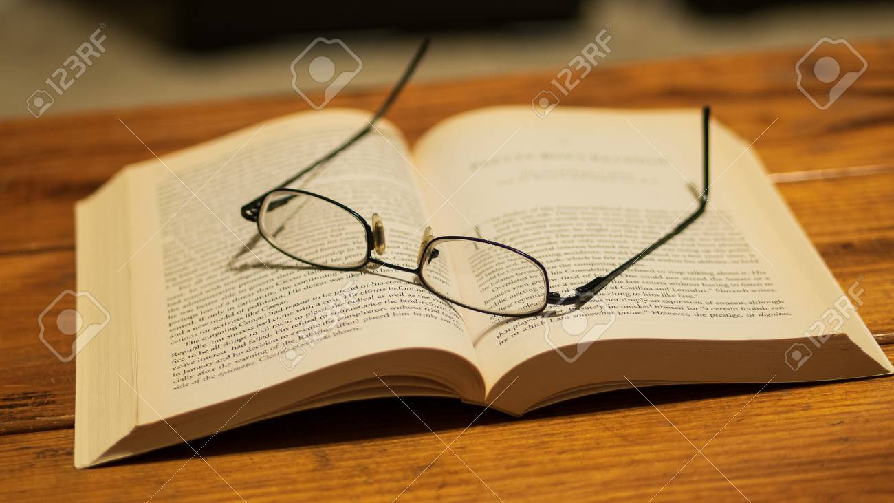 Best Music Coffee Table Books.Eye Glasses Resting On Top Of A Book Sitting On A Wooden Coffee