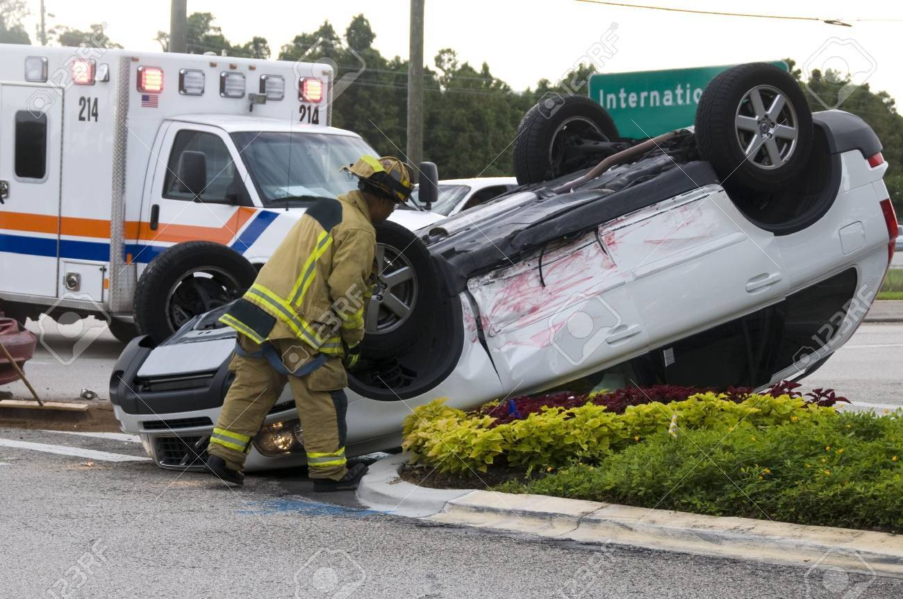 Rollover Vehicle Accident at Busy Intersection With Emergency Personnel to Assist Stock Photo - 5534848
