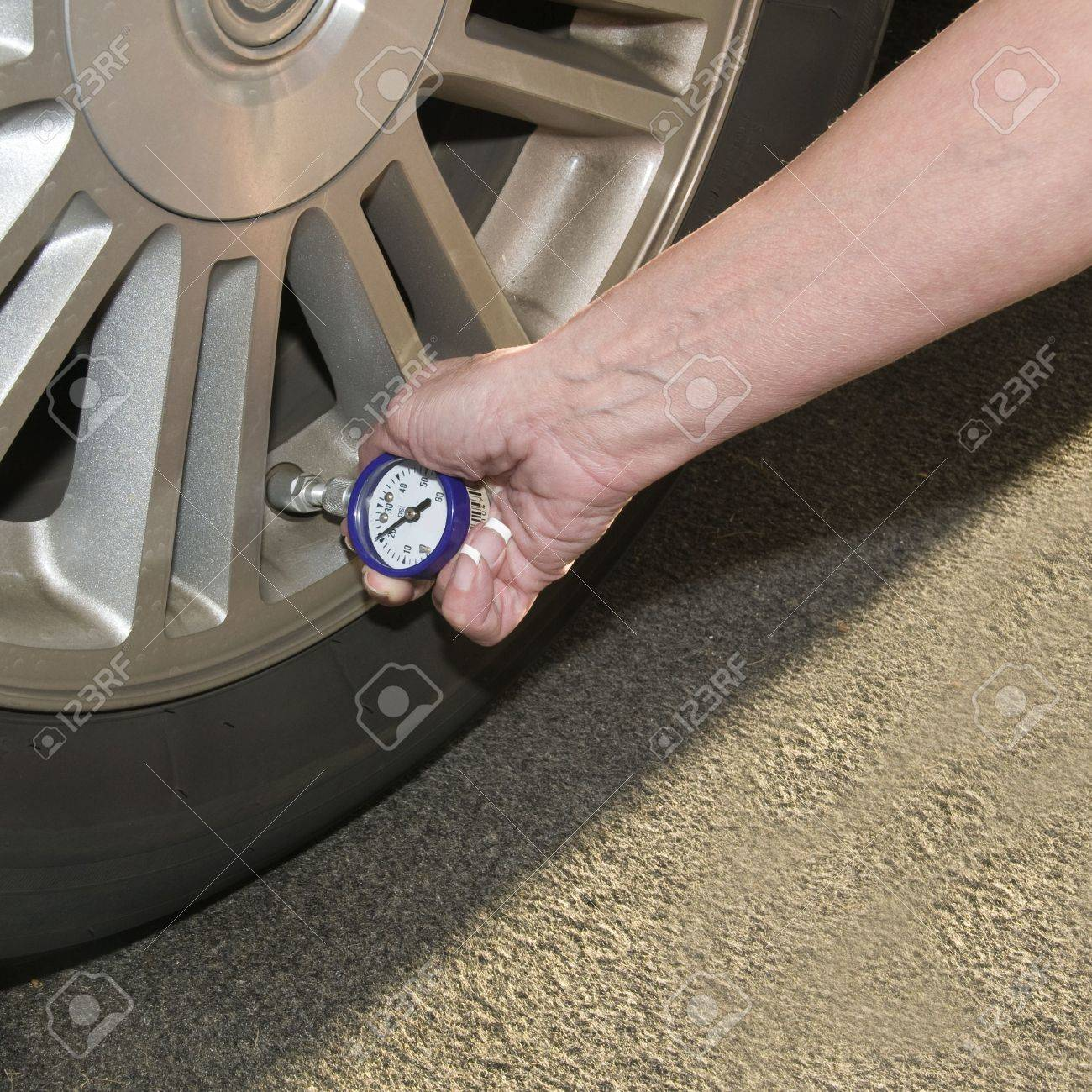 Woman checking her tire pressure to help increase her  gas mileage gauge indicates low pressure Stock Photo - 6659461