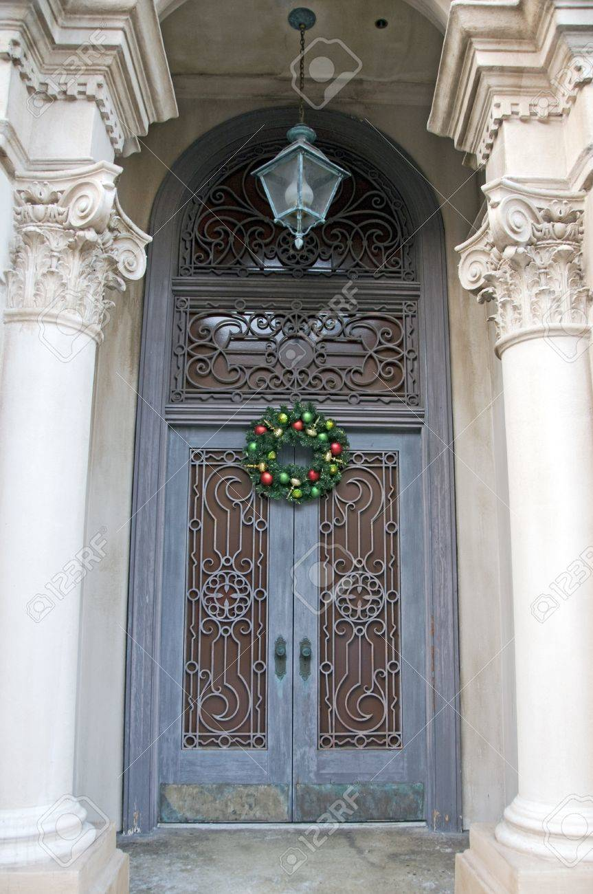 ornate iron work covering double door entrance with christmas