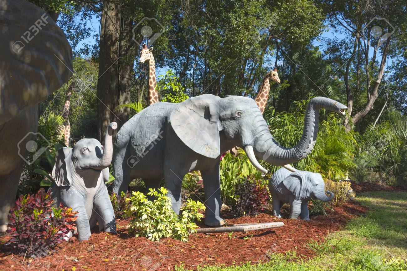 Garden Statues Of An Adult Elephant And Two Baby Elephants With Giraffes In  The Background Stock
