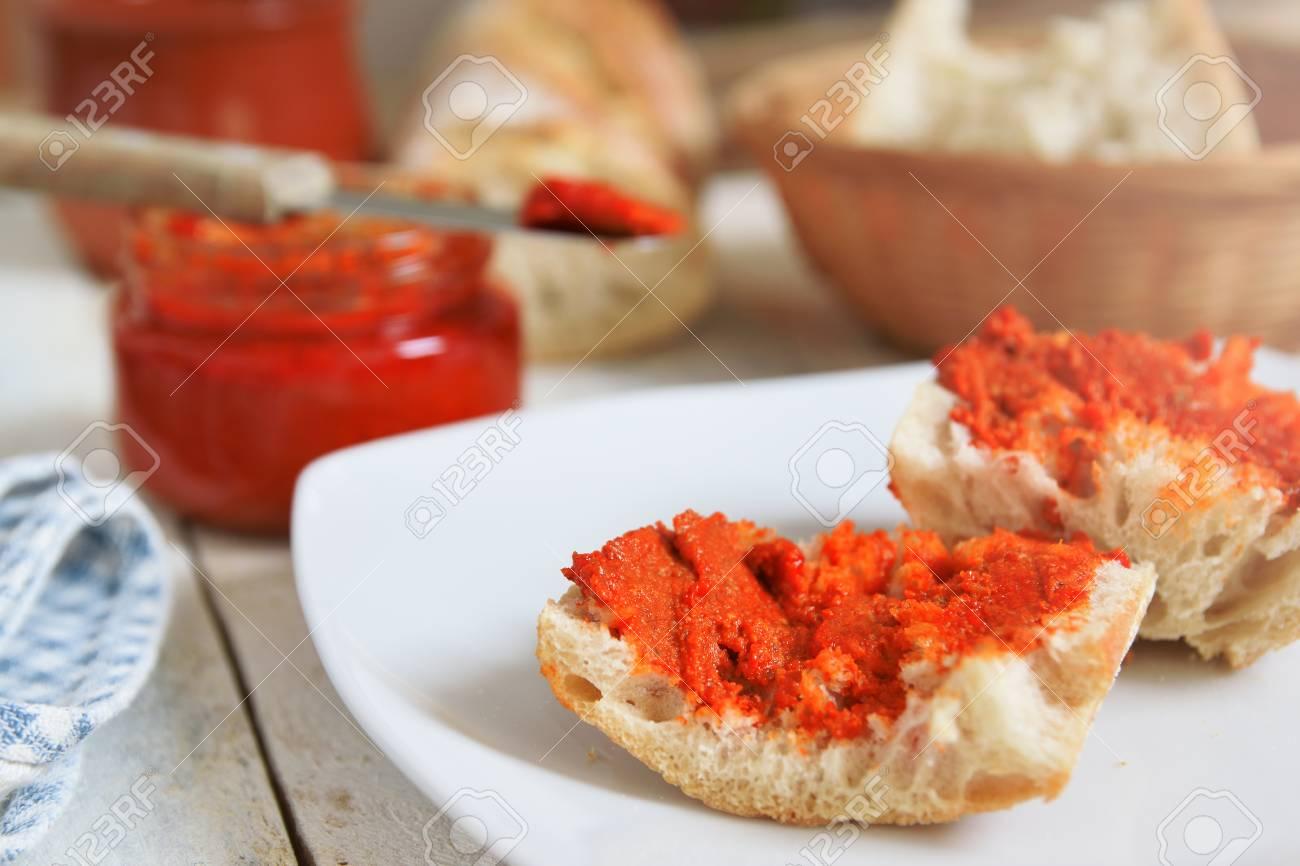 Una tipica busta di Maiorca si è diffusa su pane rustico. Il pasto è  servito su una tavola di legno bianca in una cucina rustica.
