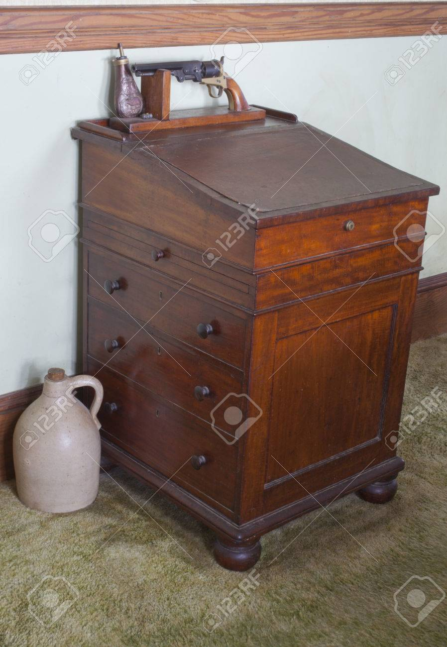 An old antique wooden desk with a gun rack and jug Stock Photo - 23017922 - An Old Antique Wooden Desk With A Gun Rack And Jug Stock Photo