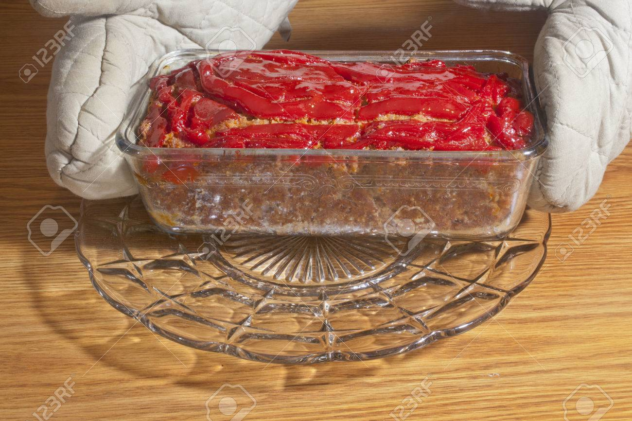 A hand with oven mitts on serving a hot meatloaf. Stock Photo - 25095005