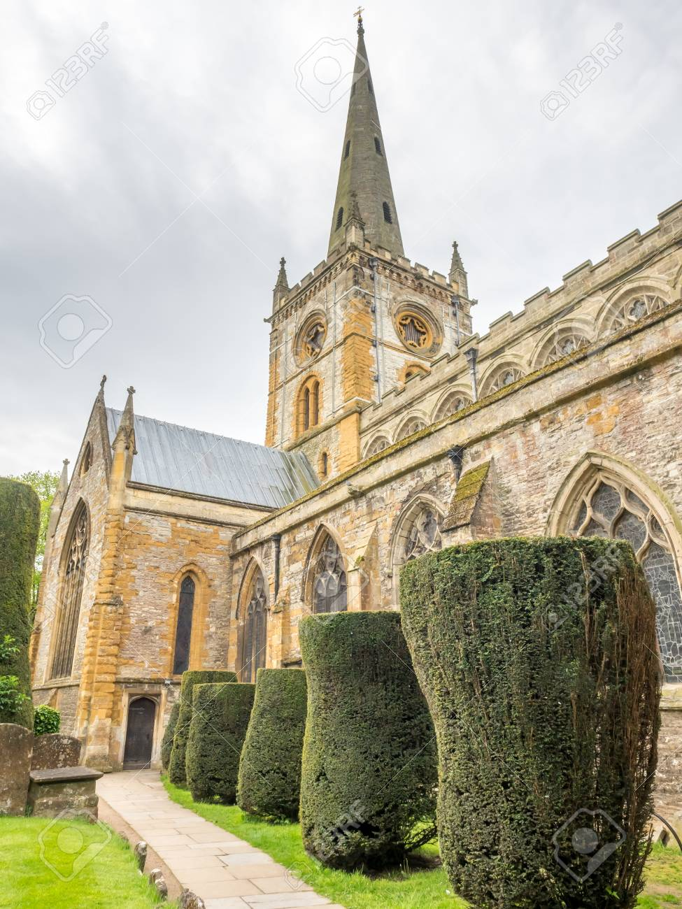 English Gothic Architecture Church In Stratford With Surrounding Park Under Cloudy Sky Stock Photo