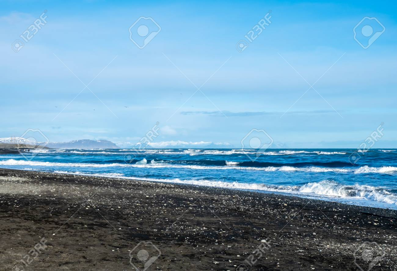 Black Sand Diamond Beach With Wave And Snow Mountains In Winter
