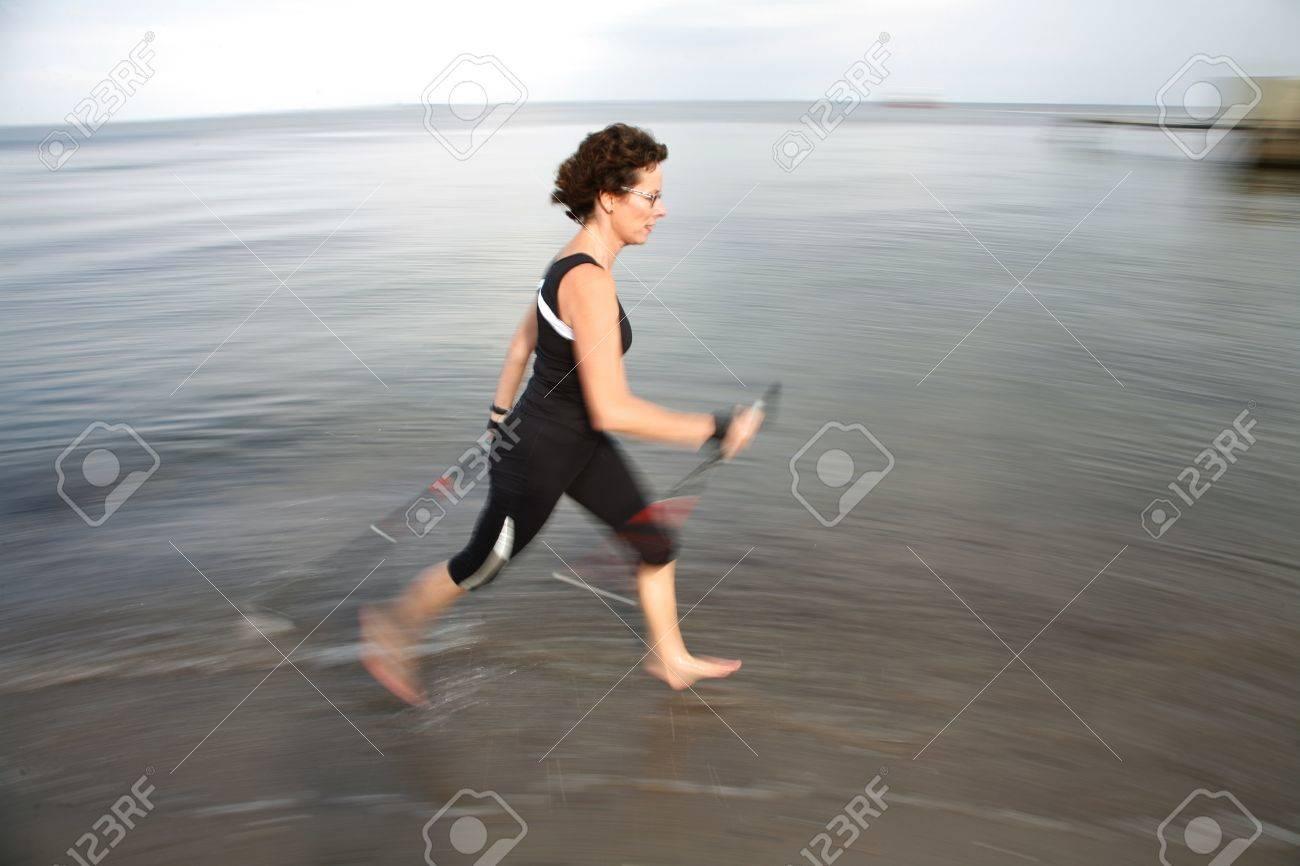 woman training nordic walking on a beach in denmark Stock Photo - 10071014