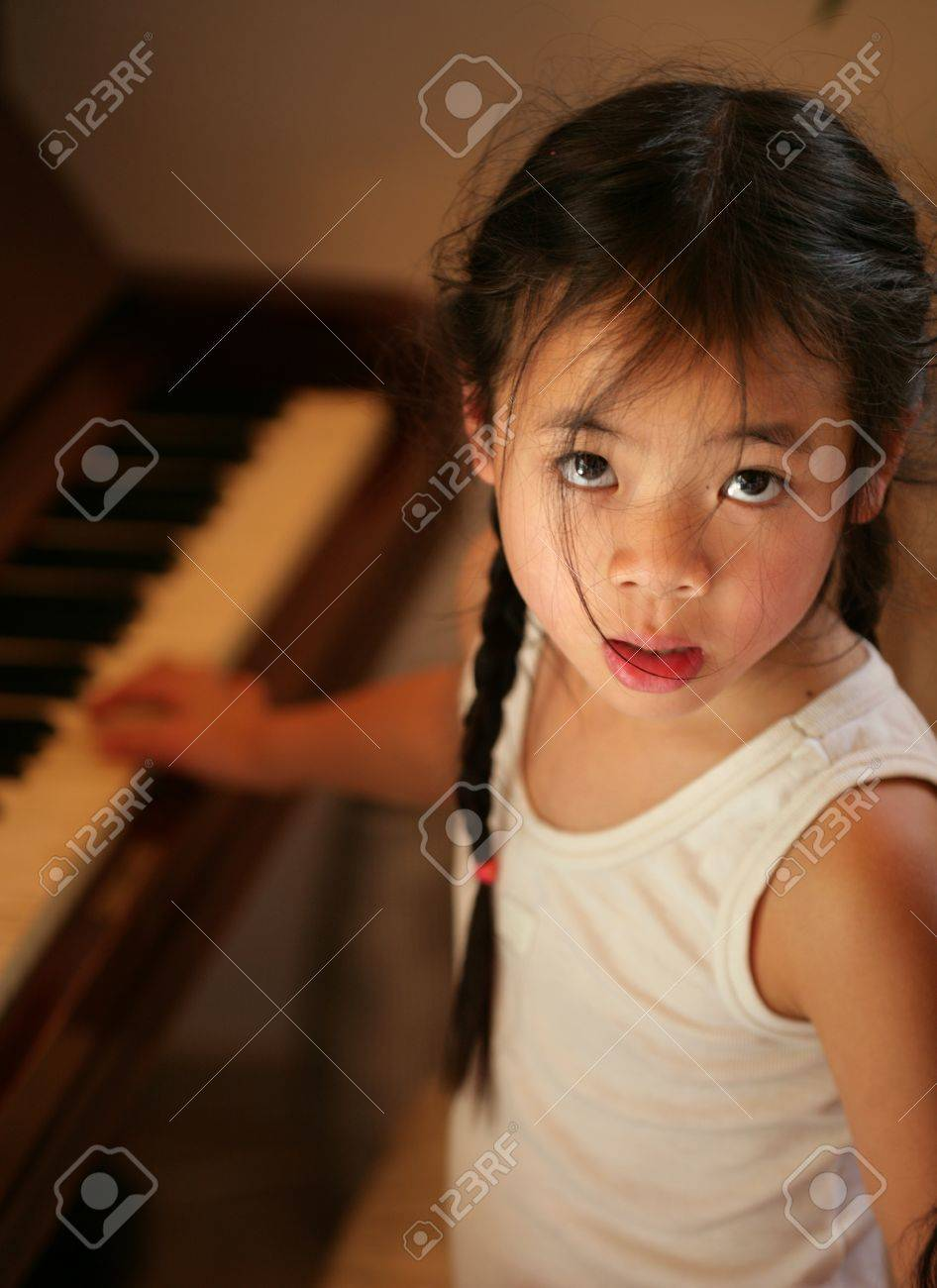 child profile  looking in fthe camera while playing piano Stock Photo - 10070906