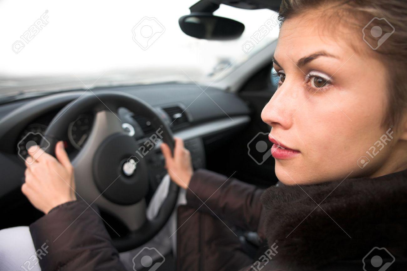 jolie femme conduire une voiture les mains sur le volant, en regardant sur le côté gauche Banque d'images - 10047815
