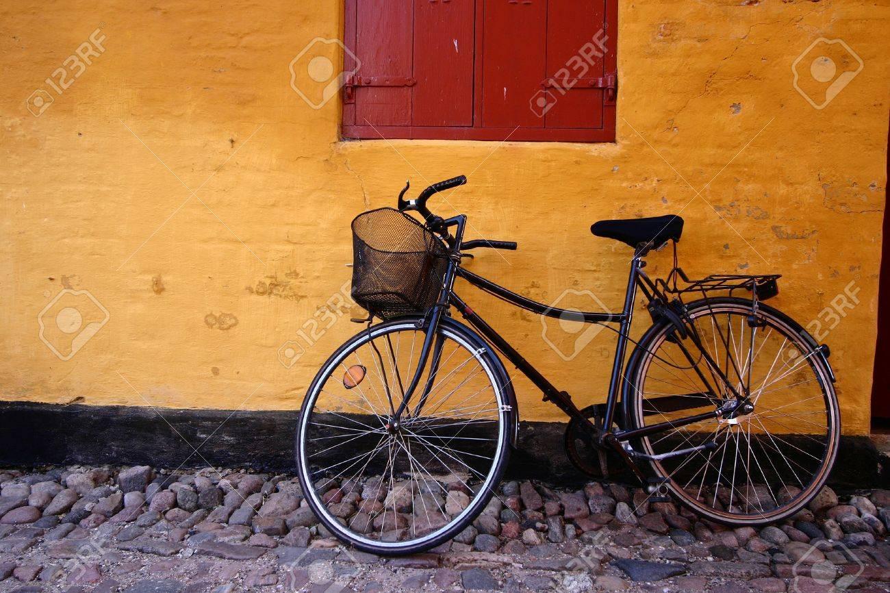 dans la rue d'un village danois de Grenaa à l'été un vélo contre un mur jaune Banque d'images - 11752291