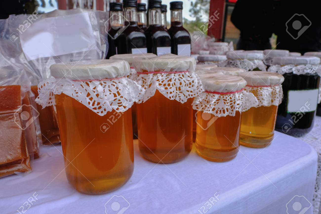 Closeup view of a selection of honey in jars with lacy tops displayed at a village fete. - 95236737