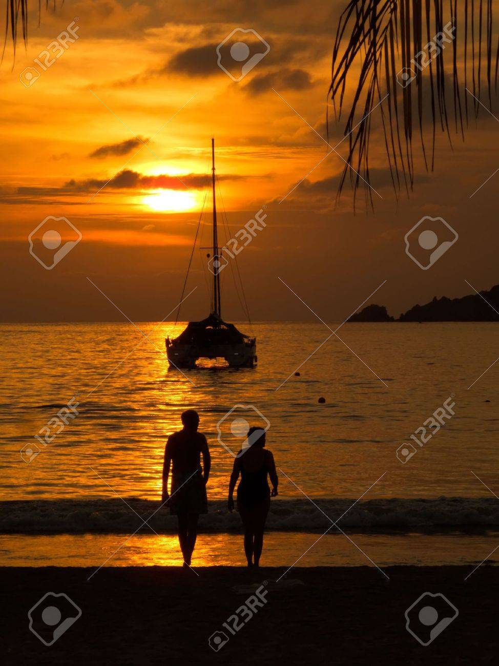Sunset with sailboat and couple sihouetted in Zihuatanejo, Mexico Stock Photo - 4220528