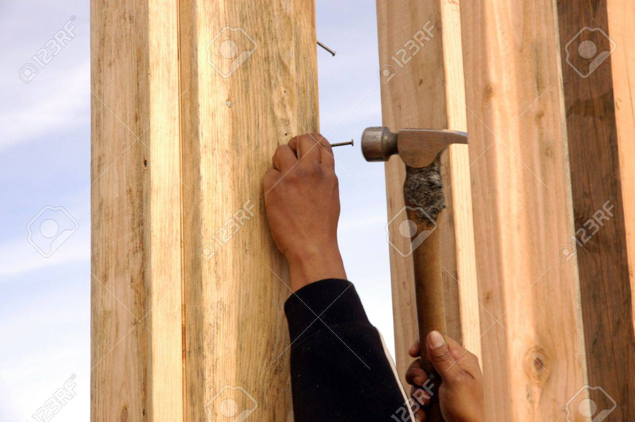 Hispanic Carpenter Hämmerte Einen Nagel In Mit Einem Framing-Hammer ...