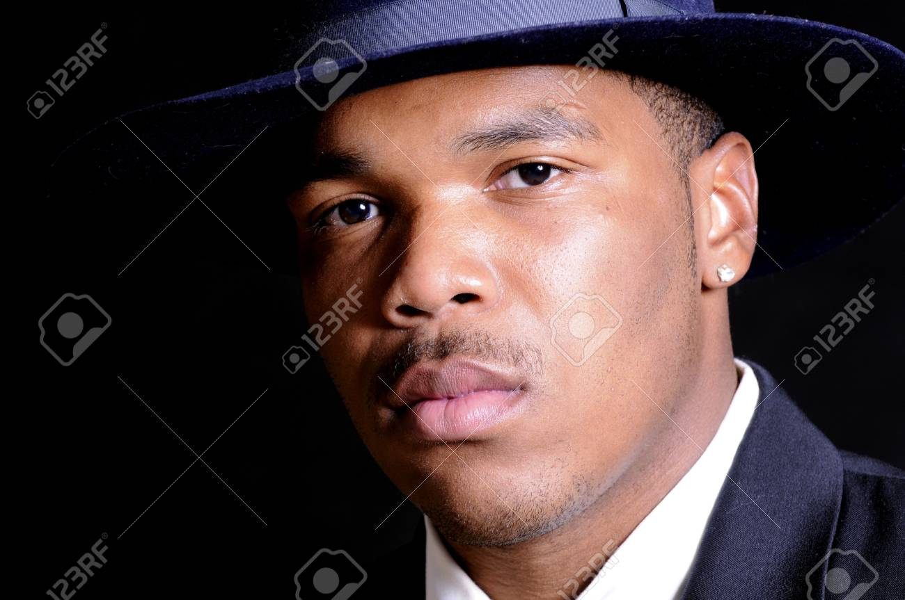 young African American man in a hat and suit over a black background Stock Photo - 3527951