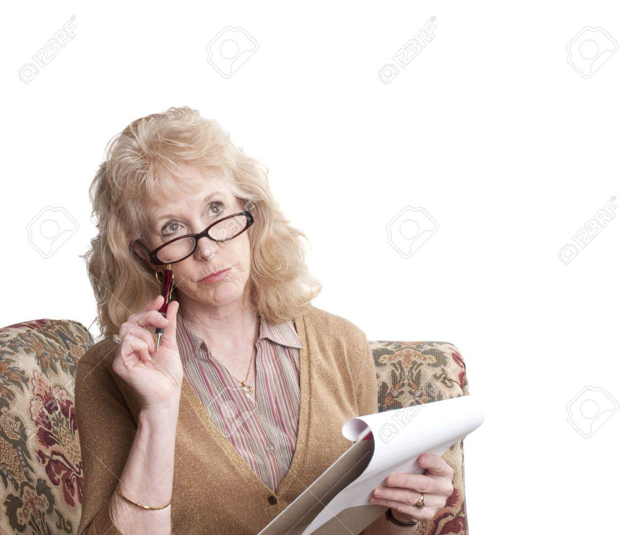 middle-aged woman with glasses on, sitting on sofa with note pad looking perplexed,  isolated on white Stock Photo - 5025762